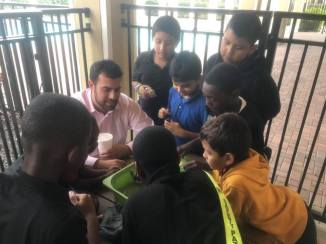 A mentor teaching boys how to play a game at the Milagro Center.