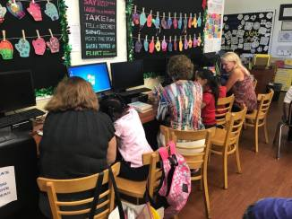 Mentors working with their mentees on homework at the Milagro Center.